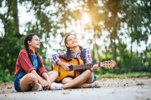 dos-chicas-relajarse-tocando-la-guitarra-y-cantar-una-cancion_1150-4112